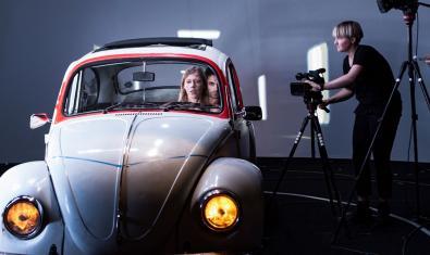 Un moment de la representació amb els actors dins d'un cotxe i un càmera filmant-los
