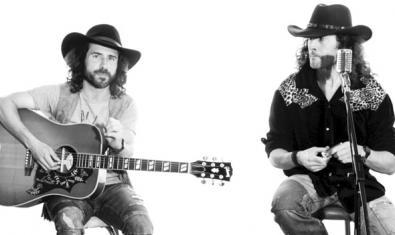 Los dos miembros de la banda con una guitarra y con sombreros de estilo country en plena actuación