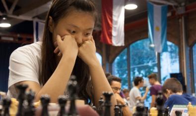 Una joven de origen chino contempla las piezas durante una partida