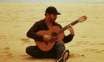 El músico con una gorra y sentado en la arena de la playa tocando la guitarra