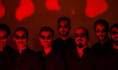 Els set integrants de la banda retratats a les fosques amb ulleres de sol i contra un fons de color vermell