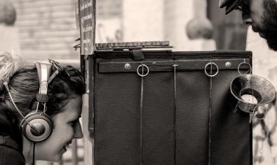 Una espectadora mira por un agujero la representación que tiene lugar dentro de una caja