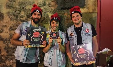 Retrato de los tres miembros de la banda de punk con su nuevo disco en las manos