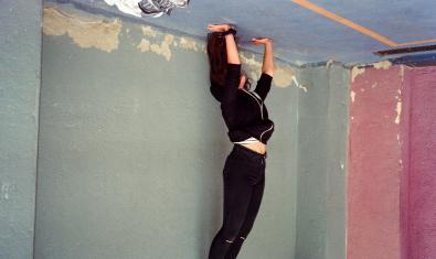 Una noia retratada de cap per avall al pati d'una escola mentre fa el pi