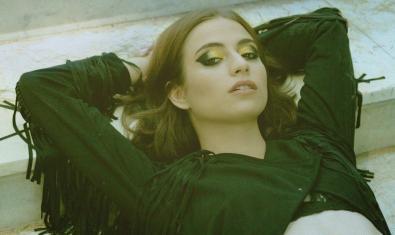 La jove cantant estirada i amb els braços darrere el cap