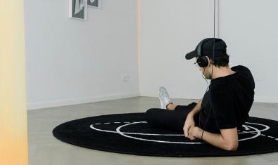 Un espectador tumbado en el suelo sobre una alfombra escucha la creación sonora de Pedro Torres