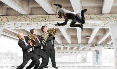 Three musicians playing while a man dressed as a wolf takes a giant leap.