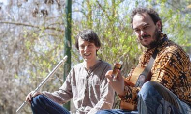 Los dos músicos que forman la banda retratados con sus instrumentos en plena naturaleza bajo los árboles