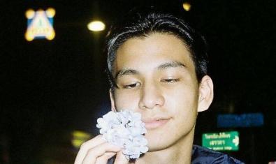 Fotografia del jove artista d'origen tailandès mirant-se una flor