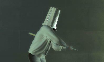 Una de les protagonistes amb un cubell al cap i un pal a la mà en un moment de la representació