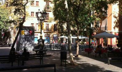Una imatge d'una plaça del Poble-sec a la tarda amb els veïns i veïnes asseguts als bancs