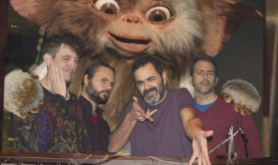 Los cuatro integrantes de la banda retratados con un gremlin gigante a sus espaldas