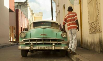 Un joven cubano de espaldas pasa junto a un coche de los años 50