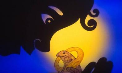 Fotografía de una escena del espectáculo de sombras. Un niño con una rana en la mano.