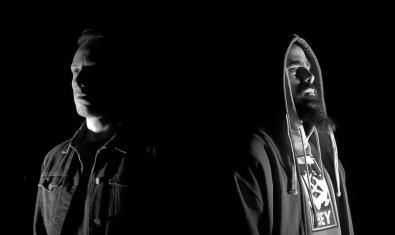Fotografia en blanc i negre dels dos components d'aquest duet retratats en la foscor i mirant en direccions oposades