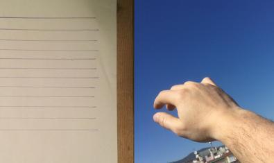 Una mà contra el paisatge de la ciutat i al costat d'un full amb una llista