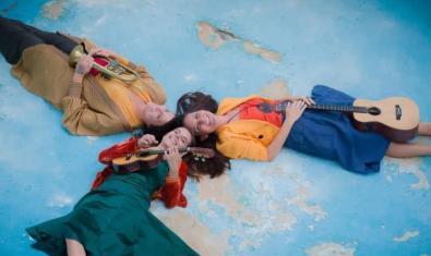 Les tres artistes estirades sobre un terra de color blau amb els caps junts