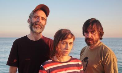 Tres de los integrantes de la banda retratados ante el mar