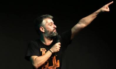 El comediant retratat amb una mà subjectant un micròfon i l'altra assenyalant cap al cel