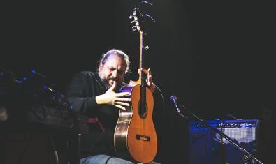 El artista flamenco tocando la guitarra con el instrumento en posición vertical durante una actuación
