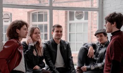 Retrat de grup dels sis membres de la banda recolzats contra una finestra