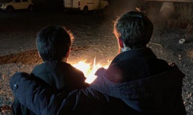 Els dos membres de la banda retratats d'esquena davant d'un foc de camp