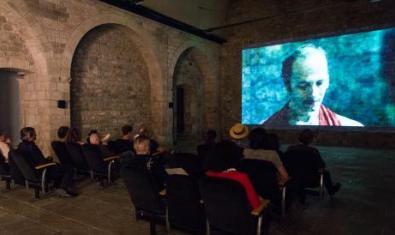 Un grup d'espectadors, veient una projecció d'una obra de vídeoart