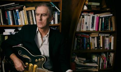 El músic retratat amb una guitarra a les mans davant d'uns prestatges plens de llibres