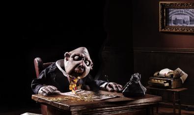 Una imagen de este montaje con un títere en una habitación oscura y escupiendo monedas por la boca sobre una mesa