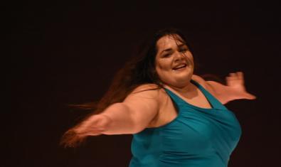 Una ballarina de formes arrodonides amb el cabell llarg evoluciona per l'escenari