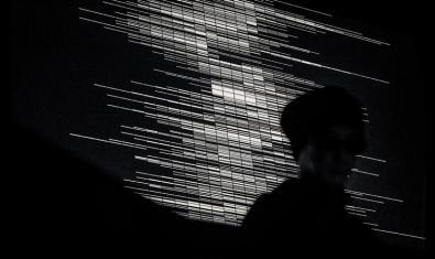 Imagen en blanco y negro que muestra el perfil de Ryoji Ikeda sobre un fondo gráfico producido por ordenador