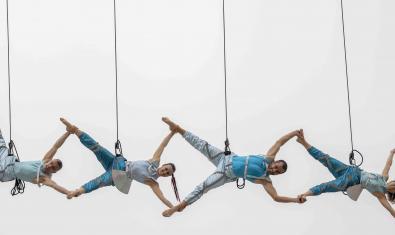 Una imatge de l'espectacle aeri que va oferir la companyia mostra quatre ballarins suspesos de cables evolucionant en el buit