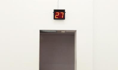 La imagen de una puerta abierta con un contador numérico en la parte superior sirve para anunciar la exposición