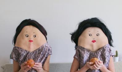 Dos muñecos inquietantes se miran sentados en un sofá mientras comen una pieza de fruta