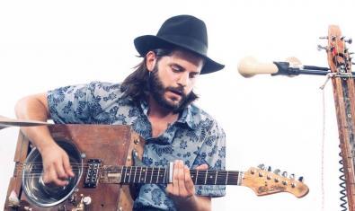 L'artista de blues retratat amb un barret i tocant els seus instruments de fabricació pròpia