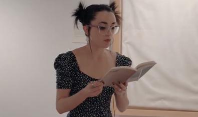 La poeta Maria Sevilla Paris con gafas y el cabello recogido leyendo sus versos ante una de las obras expuestas