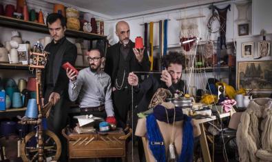 Los cuatro miembros de la banda retratados en una habitación llena de trastos