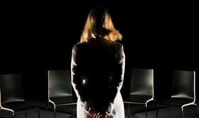 Retrat de la protagonista d'esquenes i davant de quatre cadires buides