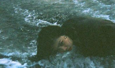 Retrat de l'artista japonesa estirada en una platja al lloc on trenquen les ones