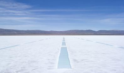 Una imagen de un paisaje nevado con unas líneas que avanzan en paralelo hacia las montañas del fondo