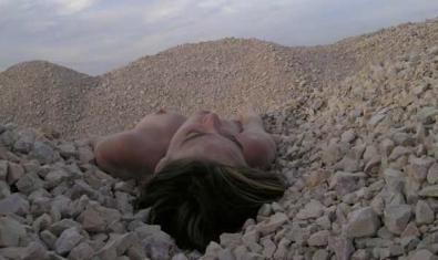 Una fotografía de Eva Davidova que muestra a una chica desnuda tumbada sobre unas montañas de piedras