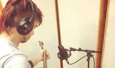 Retrat de l'artista enregistrant un tema amb els auriculars posats i tocant la guitarra