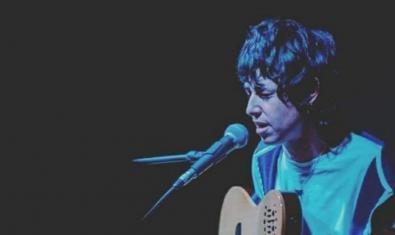 L'artista retratada tocant la guitarra i davant d'un micròfon