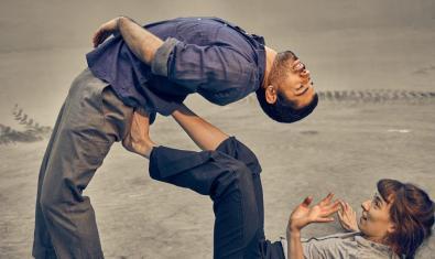 Una bailarina tumbada en el suelo soporta con los pies el peso de su compañero