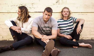 Els tres membres de la banda australiana asseguts al terra en un retrat de grup