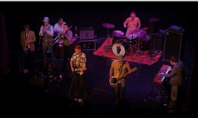 Fotografía de la banda en plena actuación captada desde arriba