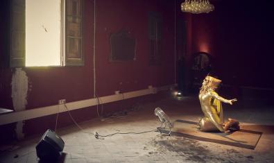Una mujer vestida de color dorado montada sobre una bombona de gas butano dorada ante una ventana abierta