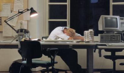 Un hombre agotado reposa la cabeza sobre una mesa de trabajo