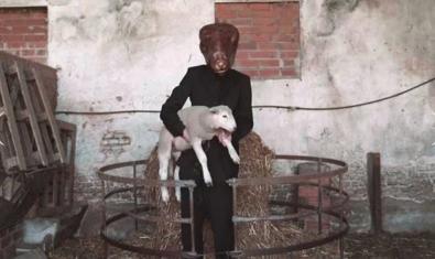Una figura humana fotografiada amb un cap d'animal posada i sostenint un be en braços