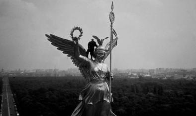 Un hombre subido en la estatua de un ángel.